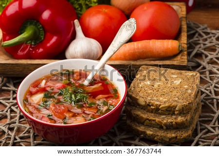 Borscht - traditional russian and ukranian beetroot soup in red bowl on wooden background.