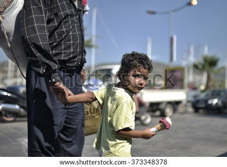 BORUM,TURKEY, 5 SEPTEMBER 2015, Syrian refugees child eating ice cream holding her father hand in Bodrum while waiting district for to switch the Greece Kos island.  - stock photo