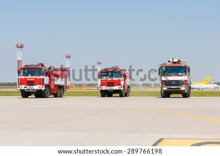 BORYSPIL, UKRAINE - MAY, 20, 2015: Fire-brigade with three red firetruck Mercedes Benz and Tatra ride on call fire suppression and mine victim assistance at Boryspil Airport, Kiev, Ukraine.  - stock photo