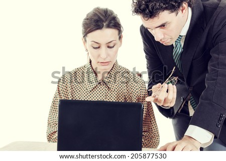 Boss and secretary working together on laptop computer, showing something on screen - stock photo