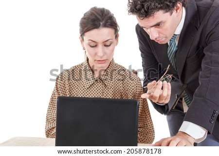 Boss and worried secretary working together on laptop computer, showing something on screen - stock photo