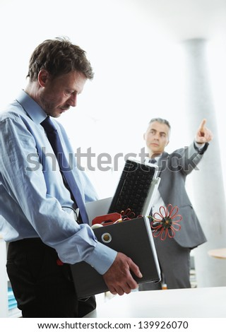Boss dismissing an employee. Dejected fired office worker carrying a box full of belongings. - stock photo