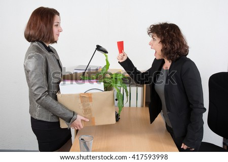 Boss dismissing an employee. Dejected fired office worker carrying a box full of belongings. Getting fired concept. - stock photo