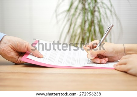 boss gives employee dismissal contract to sign - stock photo