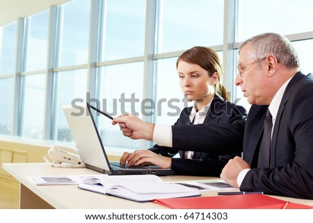 Boss helping secretary to type document correctly at meeting - stock photo