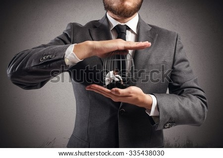 Boss holds in hands a caged man - stock photo