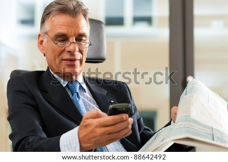 Boss in his office checking mails and reading newspapers - stock photo