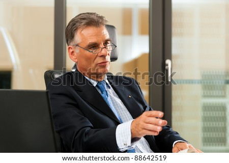 Boss in his office - presumably he is in a meeting - stock photo