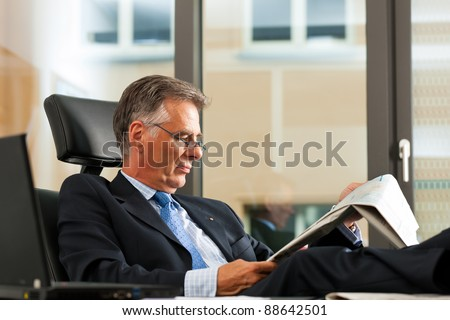 Boss in his office reading newspaper - the business section - stock photo