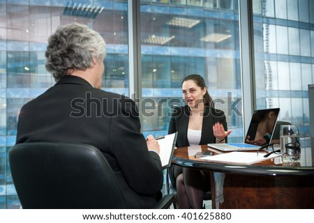 Boss interviews young employee in modern office - stock photo