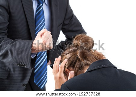 Boss is clamping his fist above frightened worker - stock photo