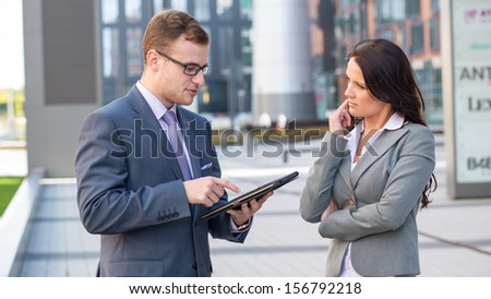 Boss pointing at tablet screen during explanation of something to secretary - stock photo