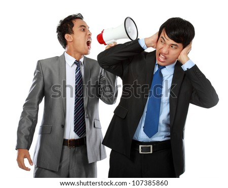 boss shouting over his employees ear, using megaphone isolated over white background - stock photo