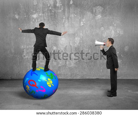 Boss using speaker yelling at businessman balancing on the colorful symbols ball, with concrete wall and floor background. - stock photo