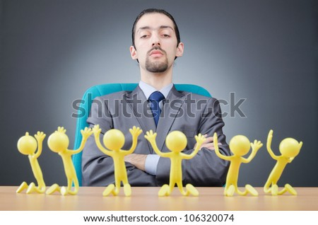 Boss with figures of his subordinates - stock photo