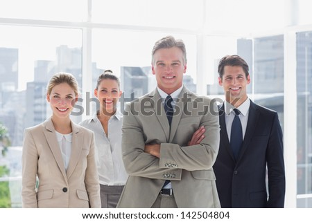 Boss with his arms folded standing with smiling colleagues behind on a modern office - stock photo