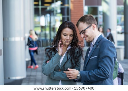 Boss with mobile phone and his secretary.