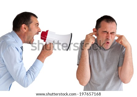 boss yelling at a subordinate through a loudhailer - stock photo