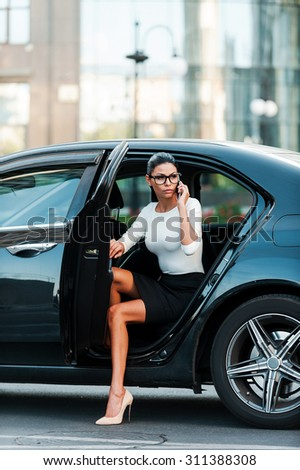 Bossy woman. Confident young businesswoman talking on the mobile phone while coming out her car - stock photo