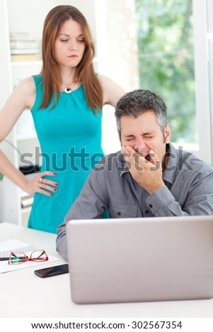 Bossy woman standing over sleepy employee in the office - stock photo