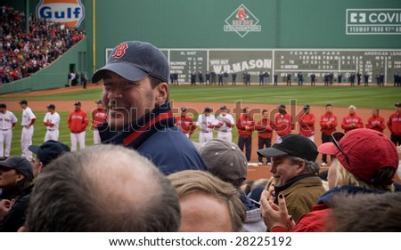 BOSTON - APRIL 7: An excited fan smiles through the crowd at the Boston Red Sox Opening Day at historical Fenway Park April 7, 2009 in Boston, Massachusetts. - stock photo