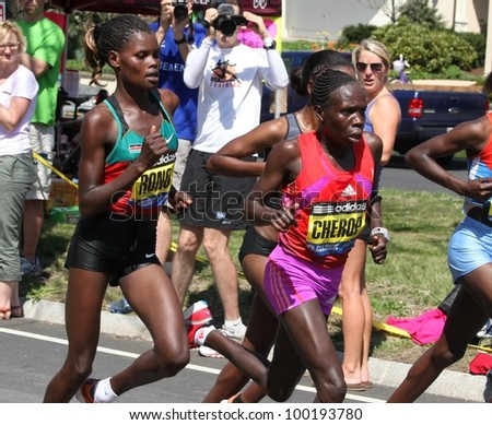 BOSTON - APRIL 16 : Sharon Cherop (purple shorts) races up Heartbreak Hill during the Boston Marathon on a hot 87 degree day on April 16, 2012 in Boston. She finished first with a time of 2:31:50. - stock photo