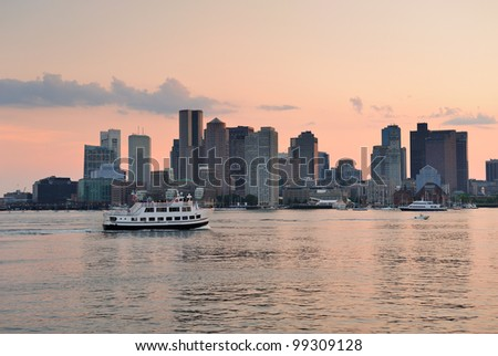 Boston downtown sunset skyline over river with skyscrapers and boat. - stock photo