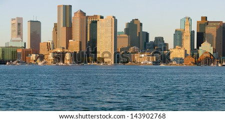 Boston Harbor and the Boston skyline at sunrise as seen from South Boston, Massachusetts, New England - stock photo