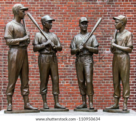 BOSTON, MA - AUGUST 10: The landmark statues of Ted Williams, Bobby Doerr, Johnny Pesky, and Dom Dimaggio attract hundreds of baseball fans to the Fenway Park in Boston, MA for souvenir photos on August 10, 2012. - stock photo