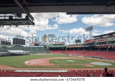 BOSTON, MA, July 4, 2017: View of Fenway Park, home of the Boston Red Sox, from a shaded seating area. People taking a guided tour appear in the foreground.