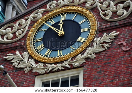 BOSTON, MASSACHUSETTS:   A handsome clock adorns the facade of the historic 1713 Old State House at the corner of State and Washington Streets is a landmark site on the Freedom Trail - stock photo