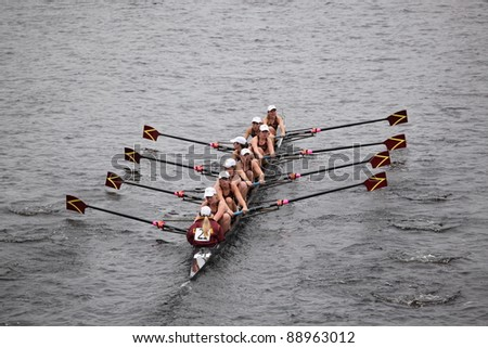 BOSTON - OCTOBER 23: Loyola Academy Rowing youth womens Eights races in the Head of Charles Regatta. Oakland Strokes won with a time of 17:12 on October 23, 2011 in Boston, MA. - stock photo