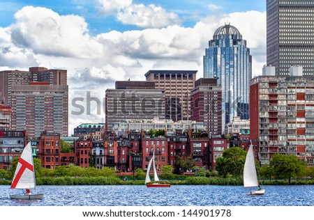 Boston's historic Back Bay neighborhood viewed from the Charles River, with recreational sailboats in the foreground. Blue sky with beautiful white clouds. - stock photo