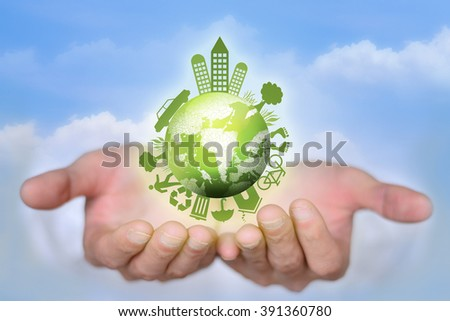 Both hands hold up the green global village - stock photo