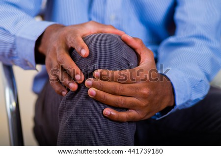 Both hands of a man making a massage on his knee, pain