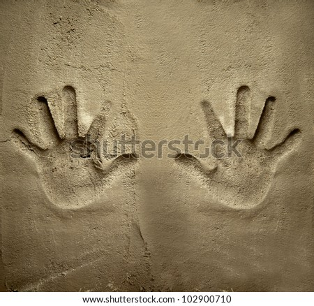 both hands print on cement mortar wall with shadow relief - stock photo