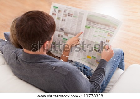 Both read recent article dealing relationships from newspaper. - stock photo