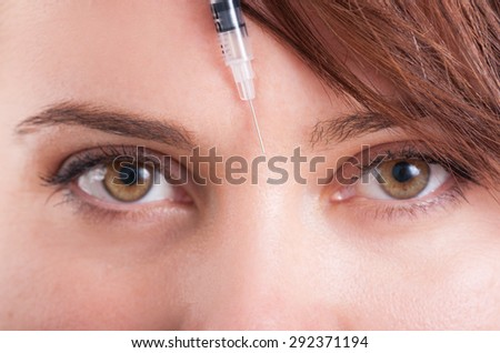 Botox syringe needle between eyes on forehead. Closeup view. - stock photo