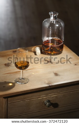 Bottle and a glass of brandy on a vintage wooden table with closed drawer