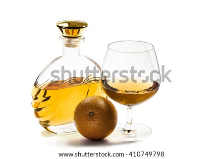 Bottle and a goblet of brandy with an orange on a white background - stock photo