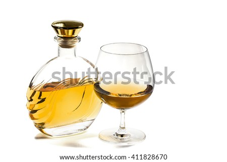Bottle and a snifter of brandy on a white background - stock photo