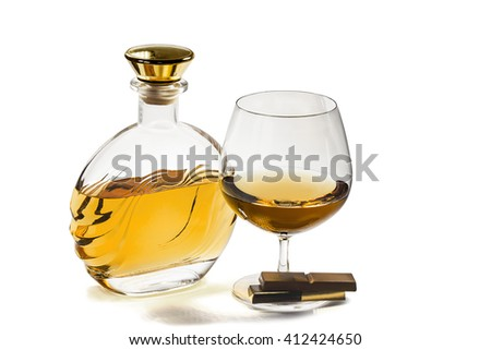 Bottle and a snifter of brandy with a chocolate on a white background - stock photo