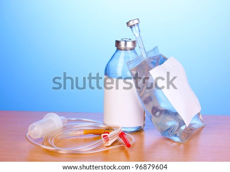 Bottle and bag of intravenous antibiotics and plastic infusion set on wooden table on blue background - stock photo