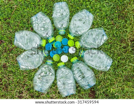 Bottle and cap water left on the grass waiting for new recyclable.  - stock photo