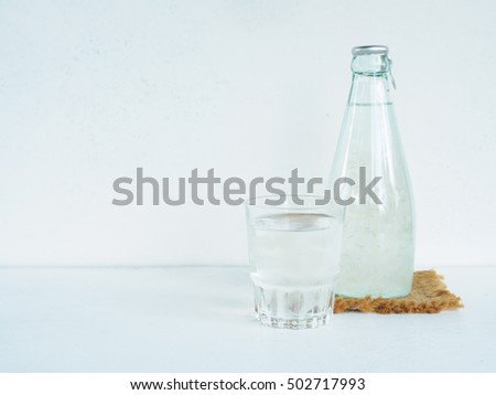 Bottle and  glass health drink of grape juice or aloe vera on white desk with copy space
