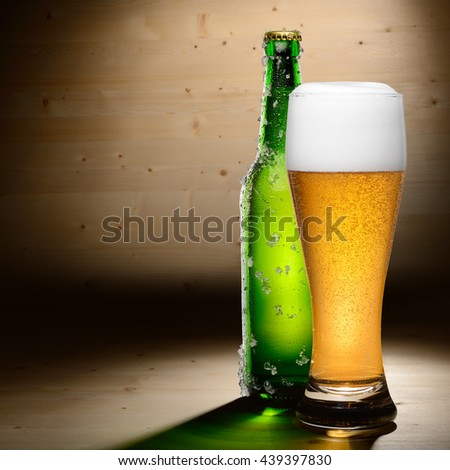Bottle and glass of beer on wood background with copyspace - stock photo