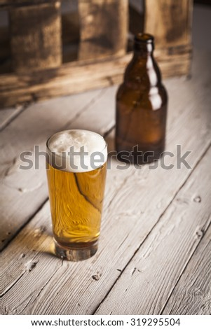 Bottle and glass of beer with wooden background