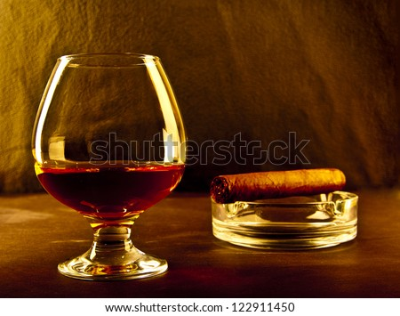 bottle and glass of brandy and cigar on black background - stock photo