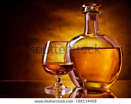 Bottle and glass of brandy on a dramatic red and yellow background - stock photo
