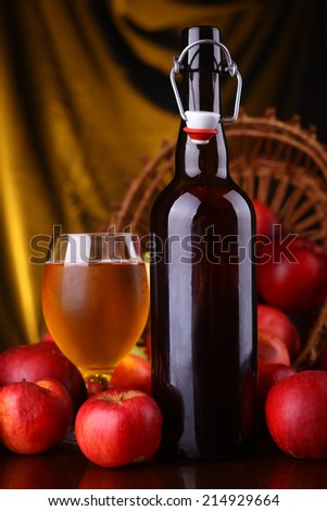Bottle and glass of cider with ripe apples over a warm background - stock photo